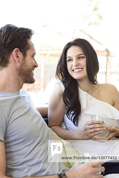 Smiling Caucasian couple relaxing with cold drinks