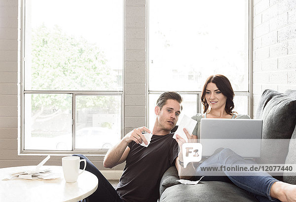 Caucasian couple using laptop on sofa