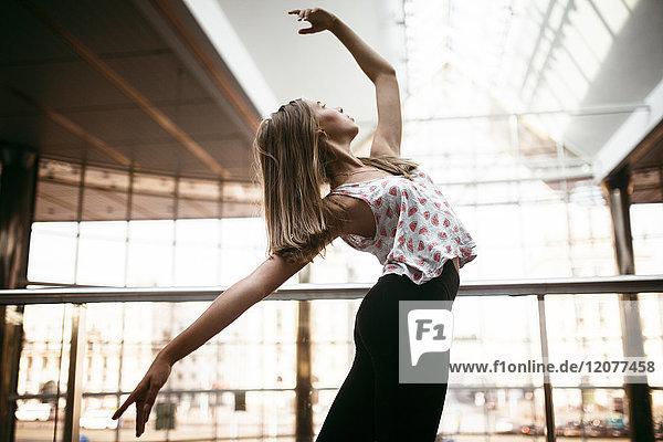 Caucasian woman dancing near railing