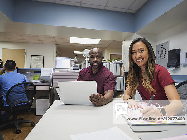 Portrait of smiling nurses with binders and hospital