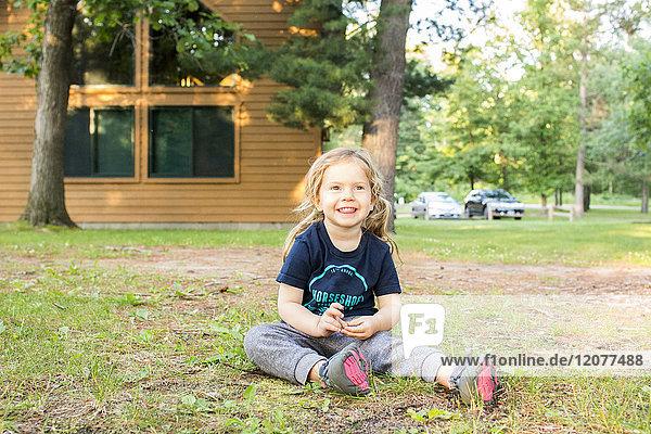 Smiling Caucasian girl sitting on ground outside house