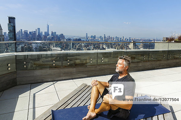 Caucasian man meditating on urban rooftop