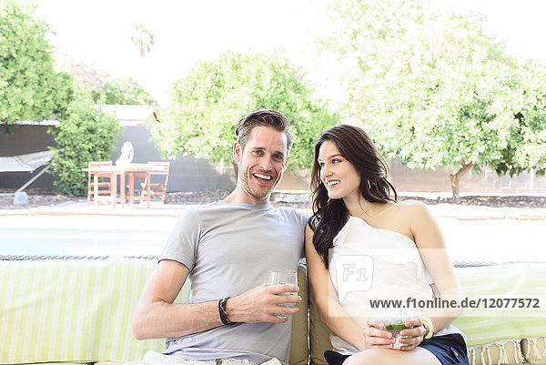 Smiling Caucasian couple relaxing with cold drinks outdoors