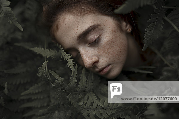 Caucasian girl with freckles resting in leaves