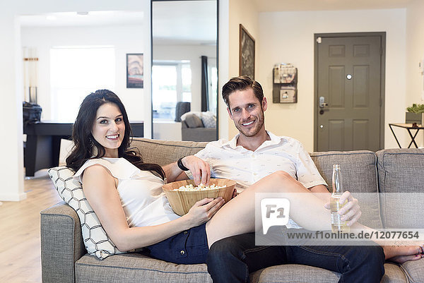 Smiling Caucasian couple relaxing on sofa with beer and popcorn