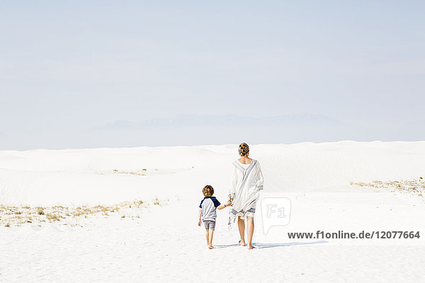 Caucasian mother and son walking in sand
