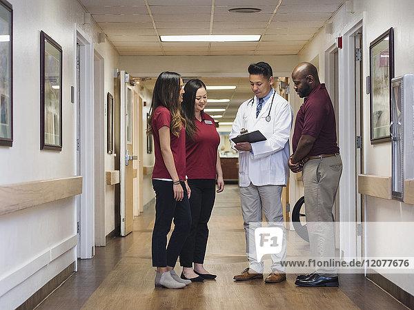 Doctor and nurses reading clipboard in hospital corridor