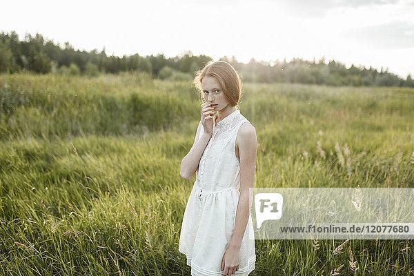 Portrait of pensive Caucasian girl standing in field