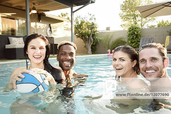 Portrait of smiling friends in swimming pool with basketball