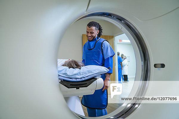 Technician talking to patient near scanner