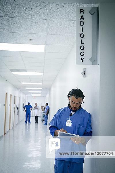 Nurse leaning on wall in hospital using digital tablet