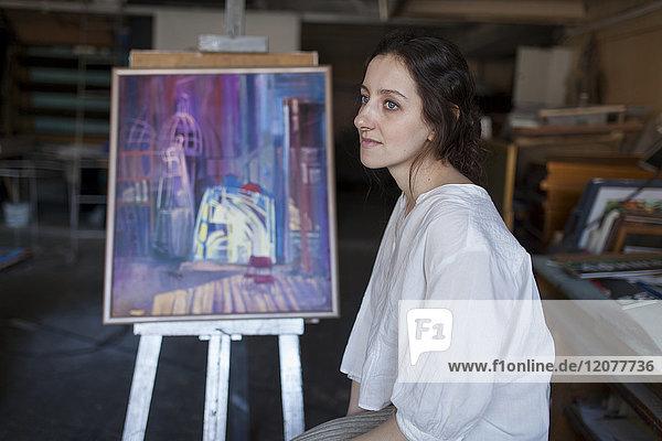 Caucasian artist sitting near paintings