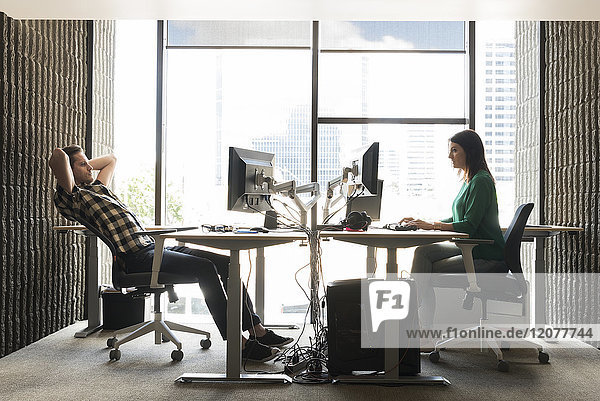 Caucasian man and woman using computers in office