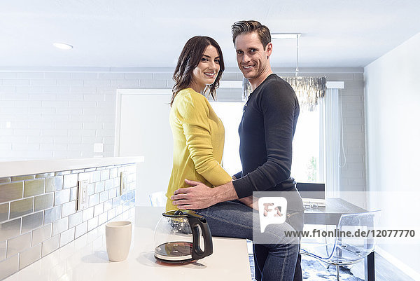 Portrait of Caucasian couple embracing on kitchen counter
