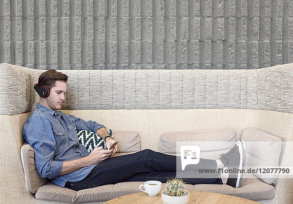 Caucasian man sitting on sofa wearing headphones texting on cell phone