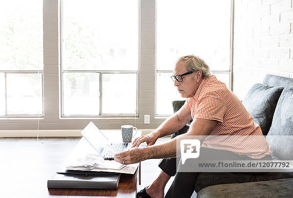Caucasian man sitting on sofa paying bills with the laptop