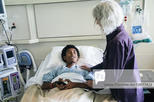 Doctor comforting boy in hospital bed holding cell phone