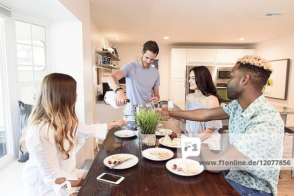 Man pouring champagne for friends at table