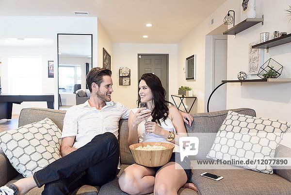 Smiling Caucasian couple relaxing on sofa with wine and popcorn
