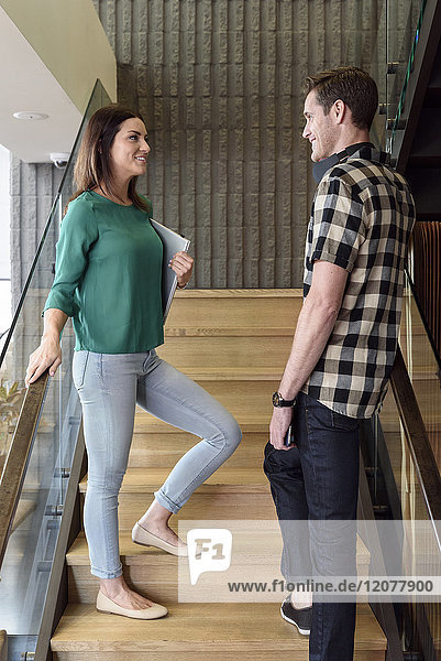 Caucasian man and woman talking on staircase