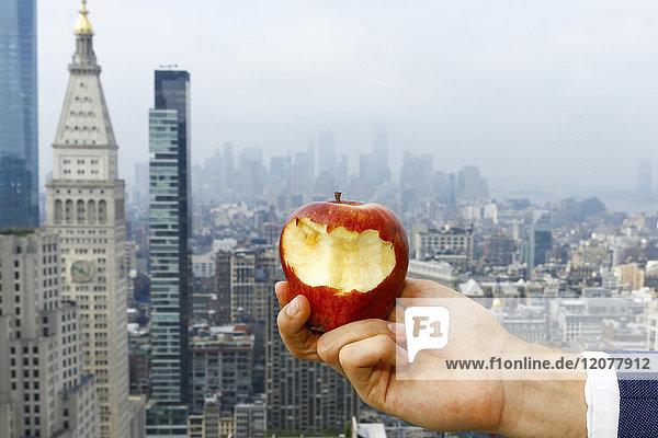 Hand of Caucasian man holding bitten apple on urban rooftop