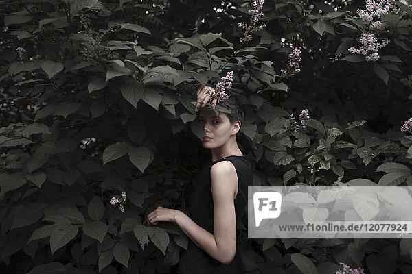 Shy Caucasian woman standing in flowering tree