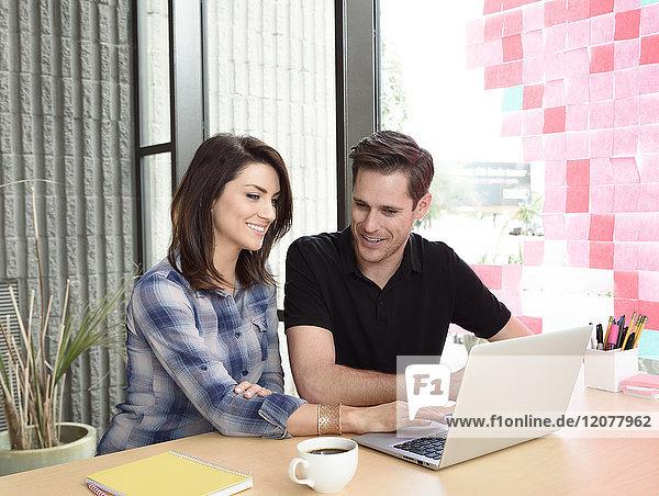 Smiling Caucasian couple using laptop