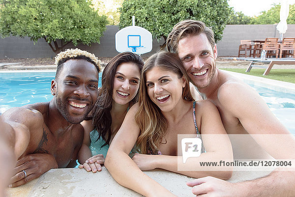 Smiling friends in swimming pool posing for selfie