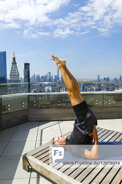Caucasian man with legs raised performing yoga on urban rooftop