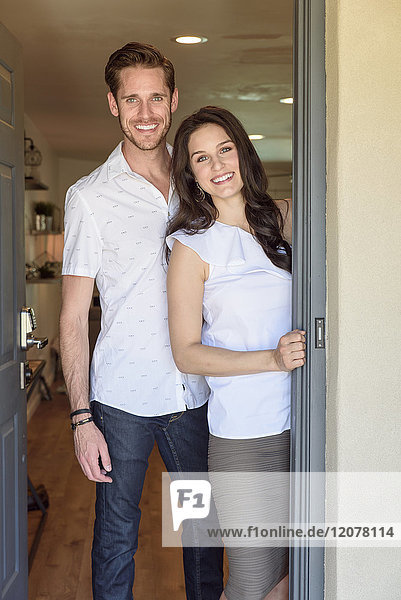 Smiling Caucasian couple posing in doorway