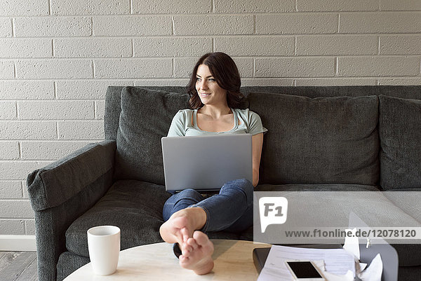 Caucasian woman sitting on sofa using laptop