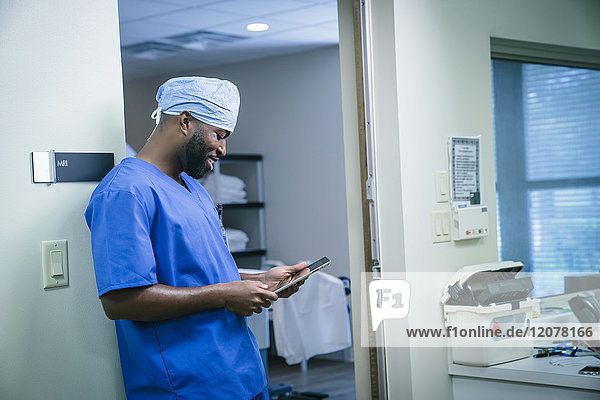 Smiling black nurse using digital tablet