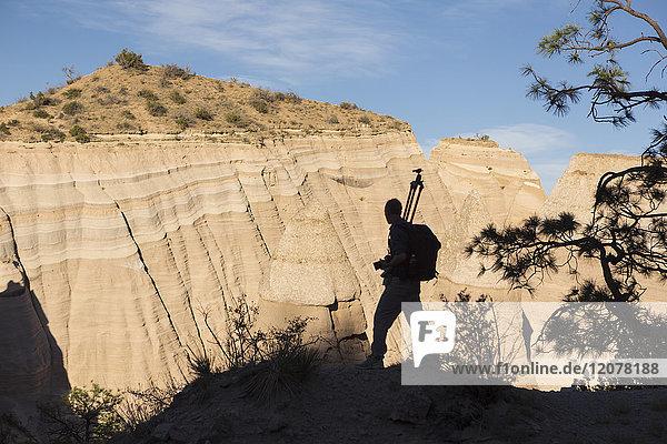 Silhouette of Caucasian man carrying tripod in desert