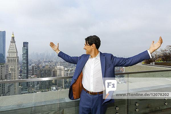 Caucasian businessman celebrating on urban rooftop