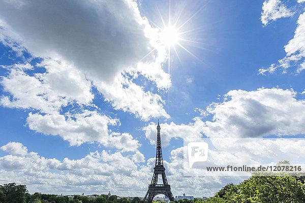 Sunbeams over distant Eiffel Tower  Paris  Ile de France  France