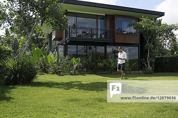 Erwachsener Mann  der im Garten vor einer modernen Villa spazieren geht  mit einem Smartphone.