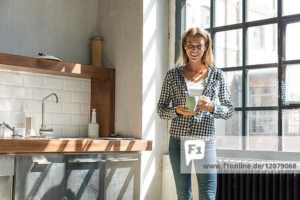 Junge Unternehmerin in der Firmenküche stehend  Kaffee trinkend