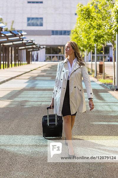 Geschäftsfrau mit Koffer im Trenchcoat