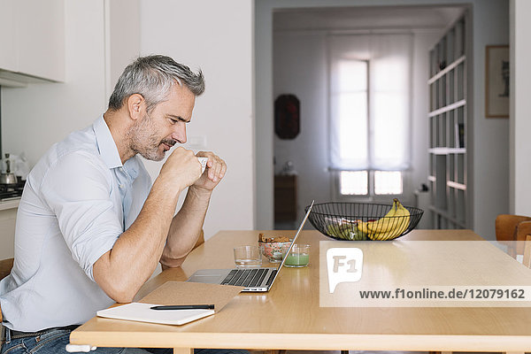 Lächelnder Mann trinkt Kaffee und benutzt Laptop im Home-Office