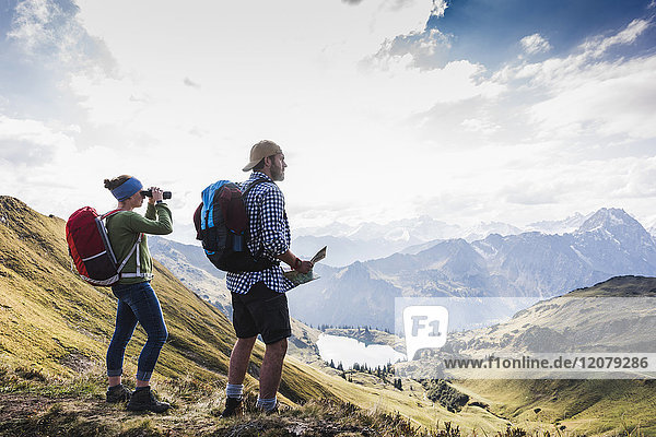 Germany  Bavaria  Oberstdorf  two hikers with map and binoculars in alpine scenery