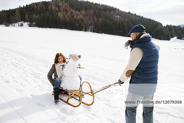 Senior couple with snowman on sledge in winter landscape