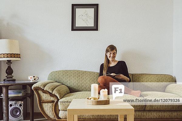 Frau sitzt auf der Couch im Wohnzimmer und schreibt in ein Notizbuch.