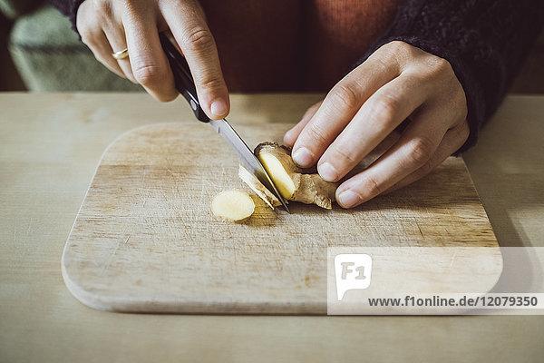 Frauenhände schneiden Ingwer auf Holzbrett  Nahaufnahme