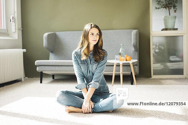 Junge Frau auf dem Boden im Wohnzimmer sitzend