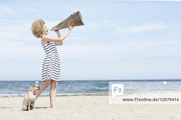 Junge Frau mit Megaphon und Hund am Strand