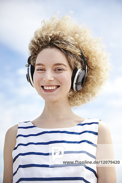 Porträt einer lachenden jungen Frau beim Musikhören mit Kopfhörern