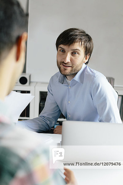 Smiling businessman with laptop at desk in office talking to colleague