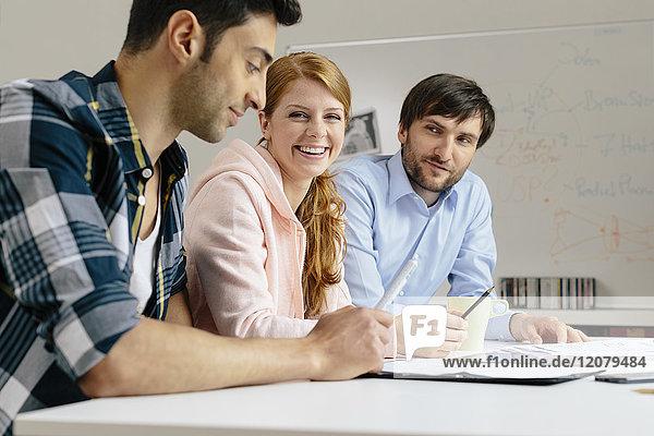 Porträt der lächelnden Kollegen am Schreibtisch im Büro