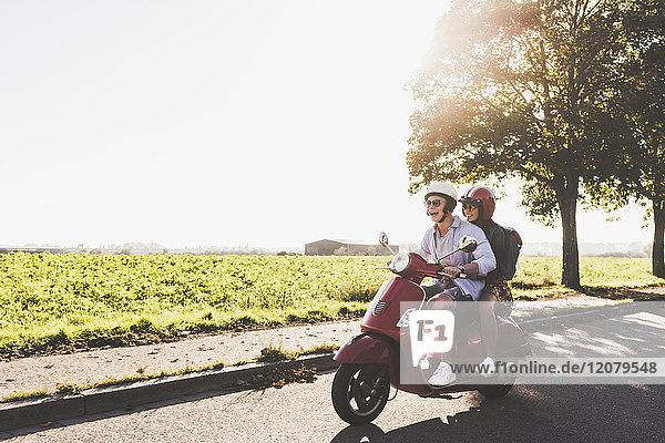 Fröhliches junges Paar beim Motorrollerfahren auf der Landstraße
