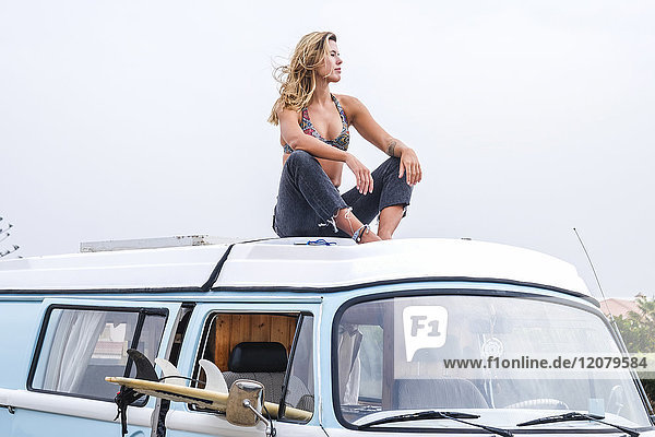 Spanien  Teneriffa  junge Frau entspannt sich auf dem Autodach des Lieferwagens
